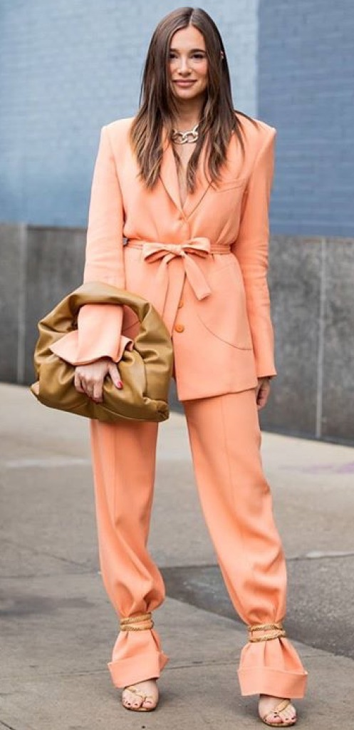 Woman wearing peach pantsuit showing spring 2020 fashion trend called stuffing.